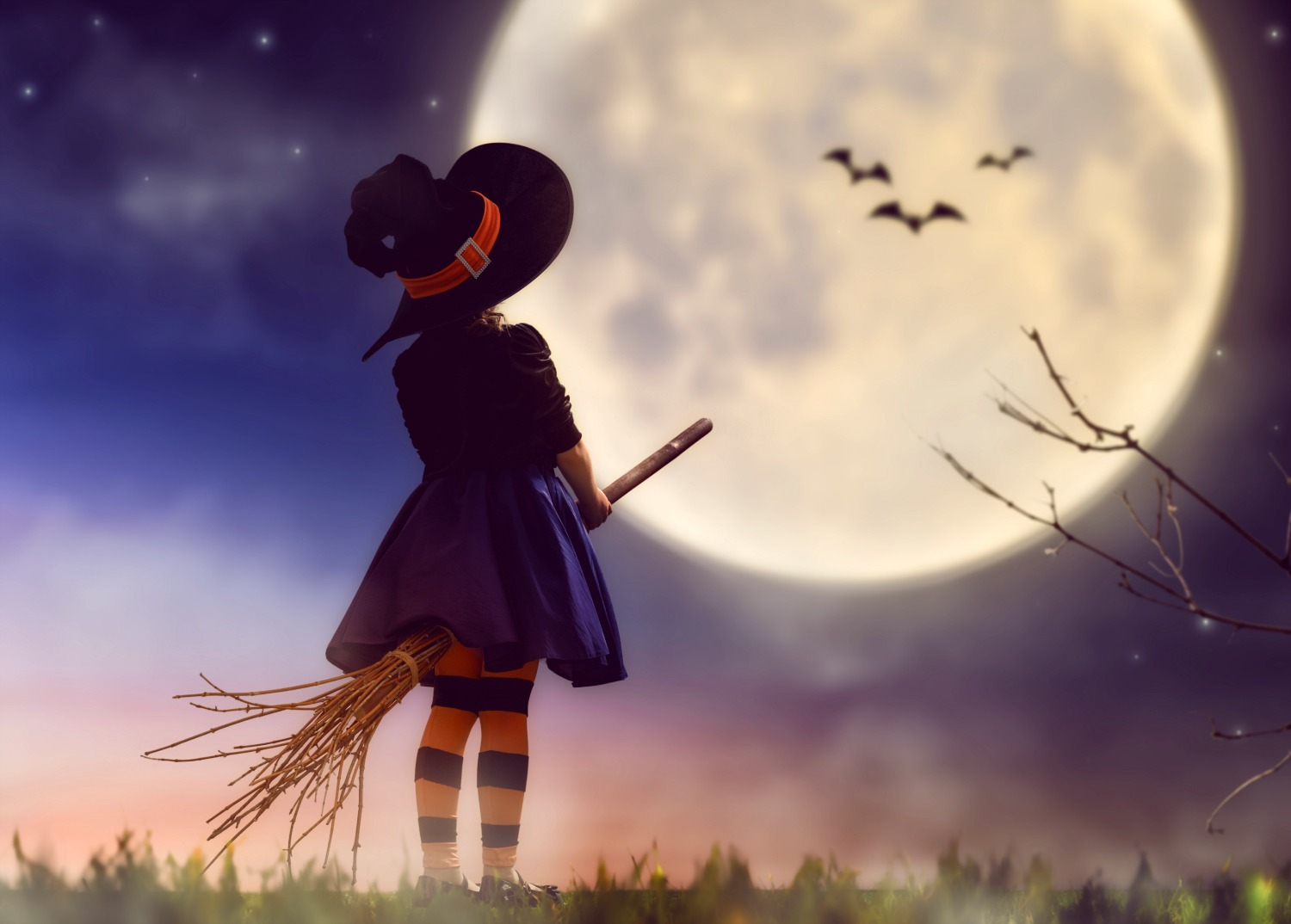 Girl in witch costume on a broomstick looking up to a moon with bats in silhouette - my top Halloween days out in the UK with kids