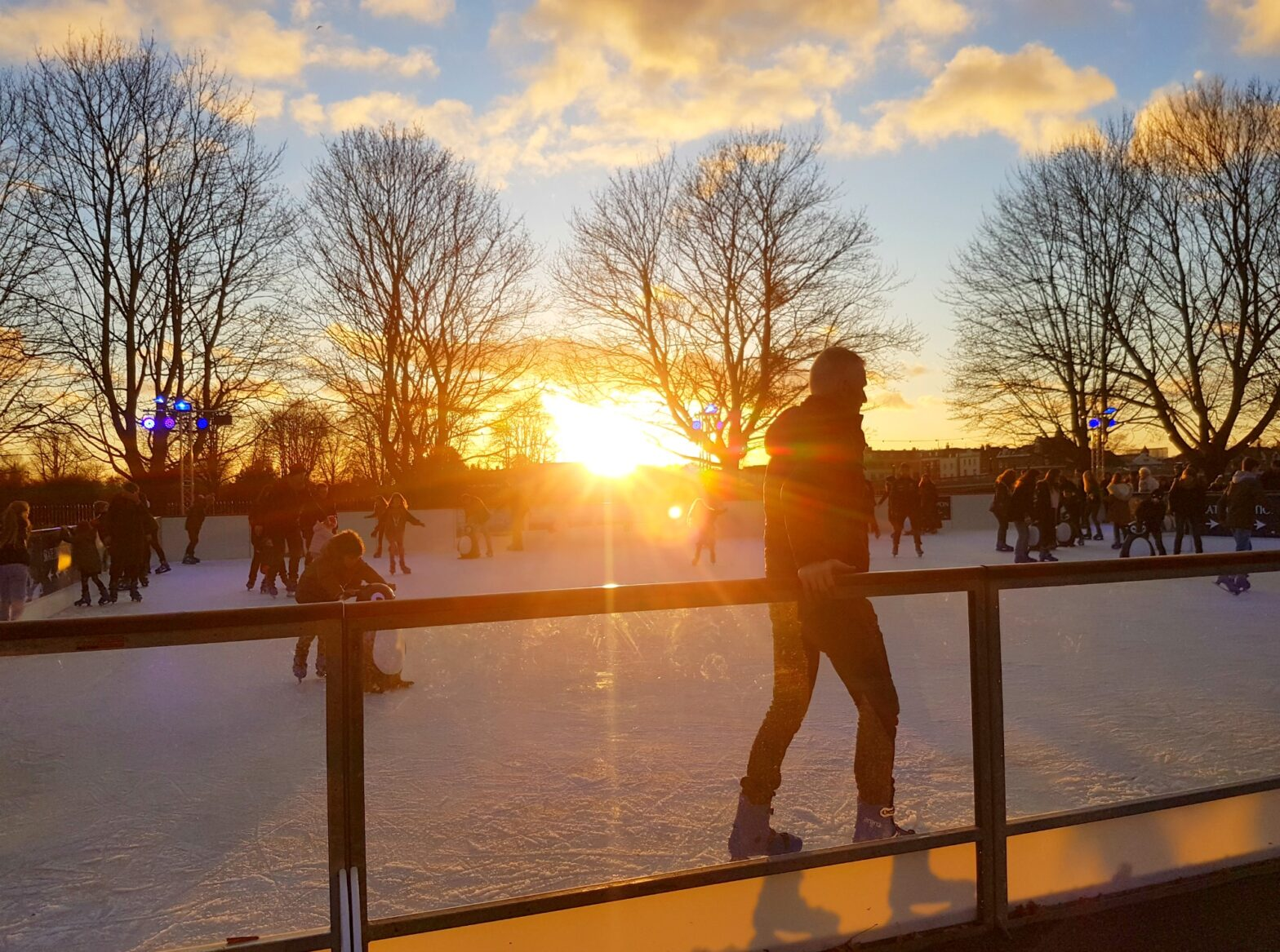 People silhouetted against the setting sun on one of the pop-up Christmas ice rinks in London at Hampton Court Palace - the best places to ice skate in London with kids