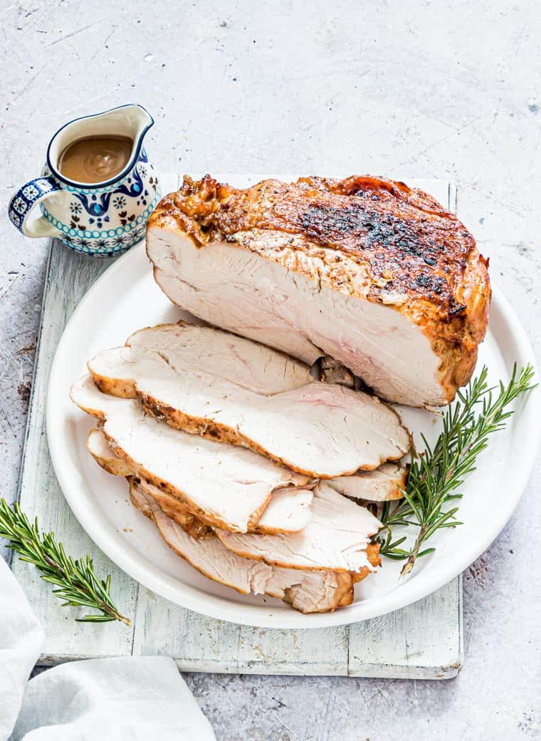 close up view of cooked turkey breast on a white platter with pitcher of gravy to the side.